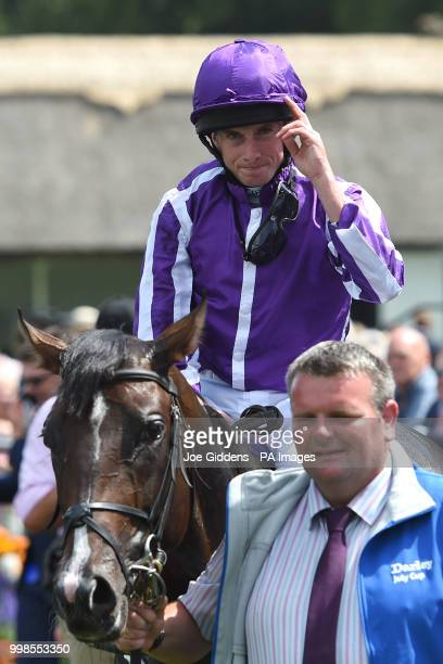 Ryan Moore celebrates on US Navy Flag after winning the Darley July Cup Stakes during day three of The Moet Chandon July Festival at Newmarket...