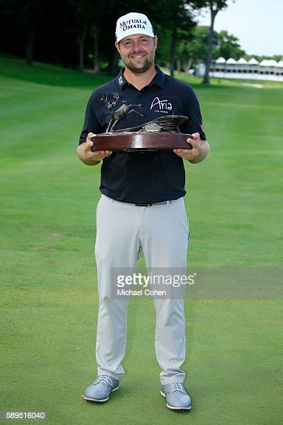 Ryan Moore holds the trophy after winning the John Deere Classic during the final round of the John Deere Classic at TPC Deere Run on August 14 2016...