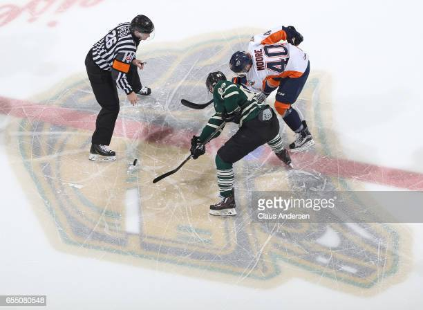 Ryan Moore of the Flint Firebirds takes a faceoff against Cliff Pu of the London Knights during an OHL game at Budweiser Gardens on March 17 2017 in...