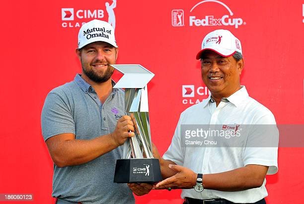 Ryan Moore of the United States receives the CIMB Classic Trophy from the Deputy Prime Minister of Malaysia Tan Sri Muhyiddin Yassin after he won the...