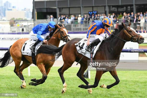 Ryan Moore riding Magic Wand leads Hugh Bowman riding Hartnell across the line to win the Seppelt Mackinnon Stakes during 2019 Stakes Day at...