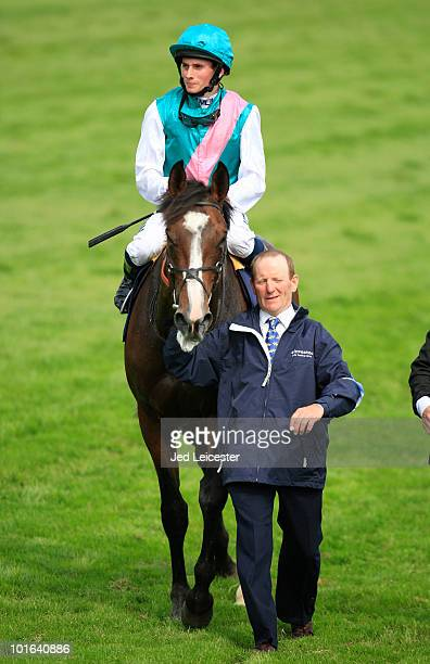 Ryan Moore riding Workforce is led into the parade ring after winning the Investec Derby race during the Investec Derby Festival at Epsom racecourse...