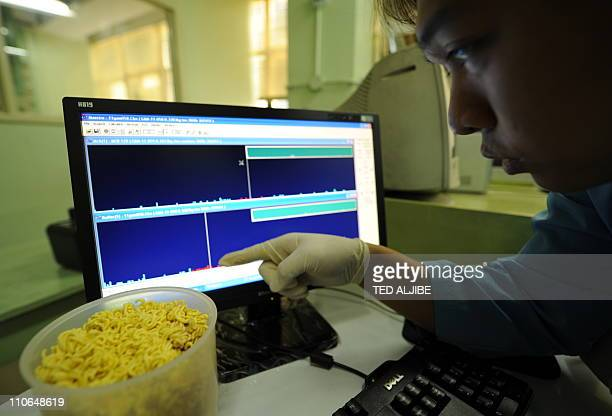 Ryan Morco Philippine science research specialist points to the spectrum on a computer screen showing the peak of radio active material on food...