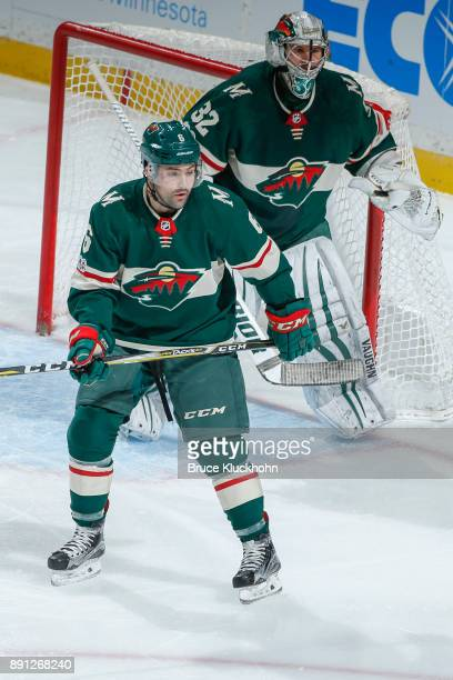 Ryan Murphy and Alex Stalock of the Minnesota Wild defend against the Calgary Flames during the game at the Xcel Energy Center on December 12 2017 in...