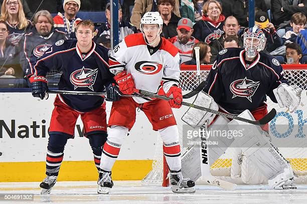 Ryan Murray of the Columbus Blue Jackets and Andrej Nestrasil of the Carolina Hurricanes battle for position in front of goaltender Joonas Korpisalo...