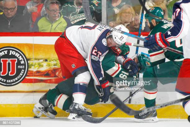 Ryan Murray of the Columbus Blue Jackets checks Luke Kunin of the Minnesota Wild during the game at the Xcel Energy Center on October 14 2017 in St...