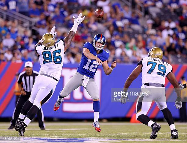 Ryan Nassib of the New York Giants passes under pressure from Michael Bennett and Ikponmwosa Igbinosun of the Jacksonville Jaguars in the second half...