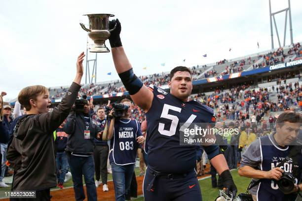 Ryan Nelson of the Virginia Cavaliers hoists the Commonwealth Cup after defeating the Virginia Tech Hokies during a game at Scott Stadium on November...