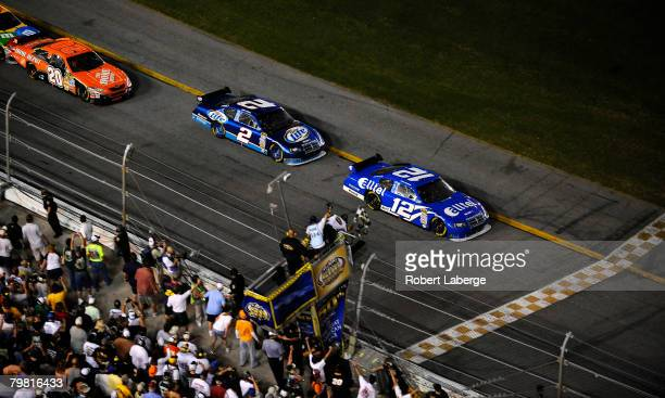 Ryan Newman driver of the Alltel Dodge crosses the finish line ahead of Kurt Busch driver of the Miller Lite Dodgeand Tony Stewart driver of the The...