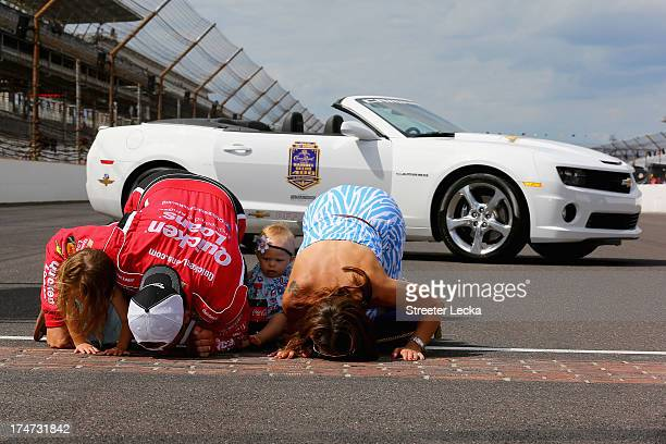 Ryan Newman driver of the Quicken Loans/The Smurfs Chevrolet kisses the bricks with wife Krissie and daughters Brooklyn Sage and Ashlyn Olivia after...