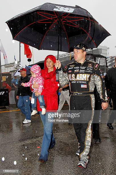 Ryan Newman driver of the US Army/Quicken Loans Chevrolet walks with wife Krissie and daughter Brooklyn back to the garage during a rain delay before...