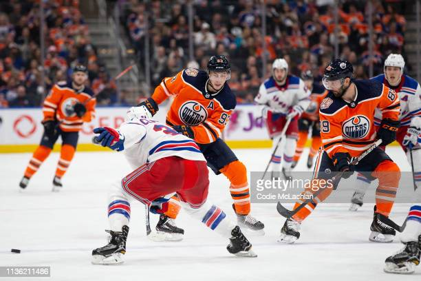 Ryan NugentHopkins and Jujhar Khaira of the Edmonton Oilers keep the puck away from Fredrik Claesson of the New York Rangers during the second period...