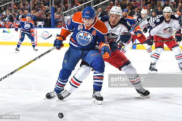 Ryan NugentHopkins of the Edmonton Oilers battles for the puck against Jack Johnson of the Columbus Blue Jackets on December 13 2016 at Rogers Place...