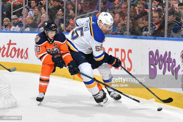 Ryan NugentHopkins of the Edmonton Oilers battles for the puck against Colton Parayko of the St Louis Blues on December 18 2018 at Rogers Place in...