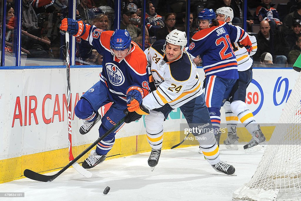 Ryan Nugent-Hopkins #93 of the Edmonton Oilers battles for the puck against Zenon Konopka #24 of the Buffalo Sabres on March 20, 2014 at Rexall Place in Edmonton, Alberta, Canada.