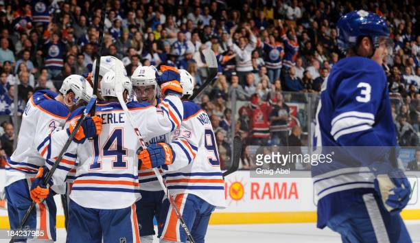 Ryan NugentHopkins of the Edmonton Oilers celebrates a first period goal with teammates as as Dion Phaneuf of the Toronto Maple Leafs skates past...