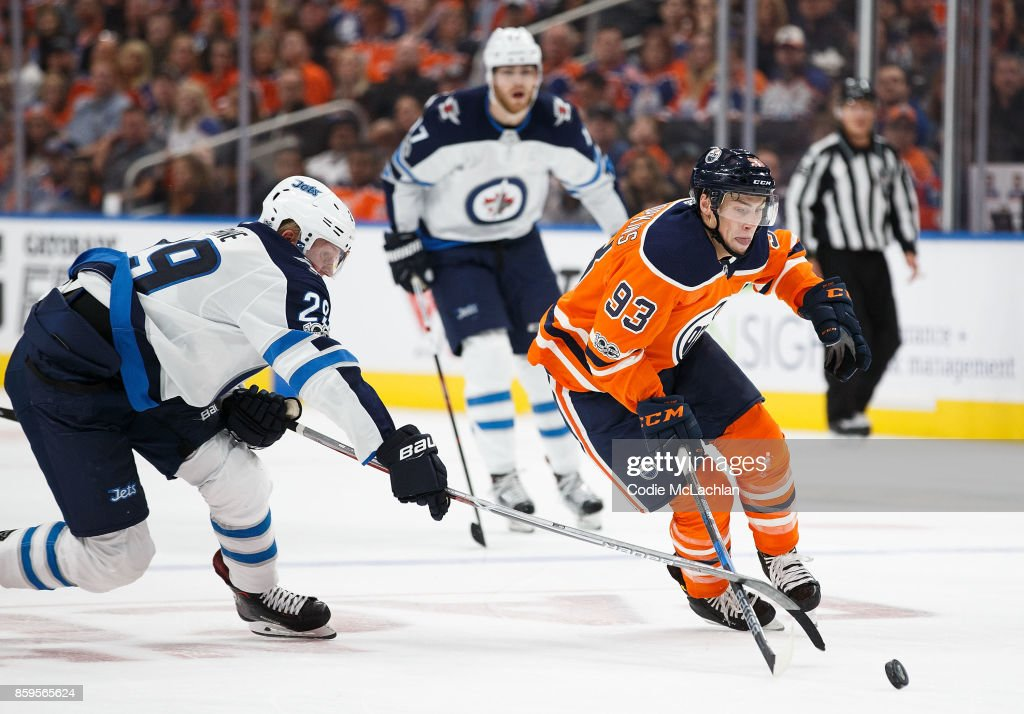 Ryan Nugent-Hopkins #93 of the Edmonton Oilers is checked by Patrik Laine #29 of the Winnipeg Jets at Rogers Place on October 9, 2017 in Edmonton, Canada.