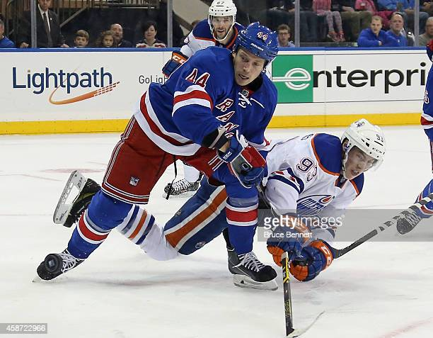 Ryan NugentHopkins of the Edmonton Oilers is knocked down by Matt Hunwick of the New York Rangers during the first period at Madison Square Garden on...