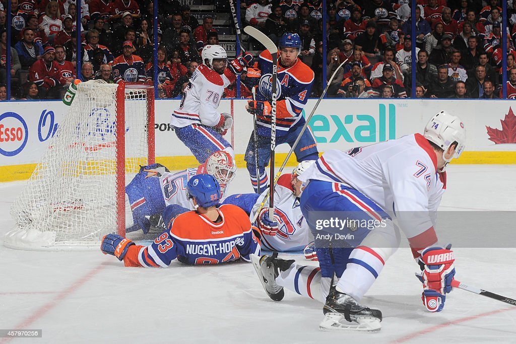 Ryan Nugent-Hopkins #93 of the Edmonton Oilers skates crashes into Dustin Tokarski #35 of the Montreal Canadiens on October 27, 2014 at Rexall Place in Edmonton, Alberta, Canada.