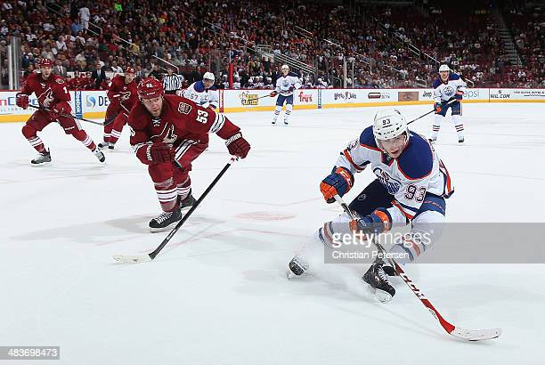 Ryan Nugent-Hopkins of the Edmonton Oilers skates with the puck ahead of Derek Morris of the Phoenix Coyotes during the NHL game at Jobing.com Arena...