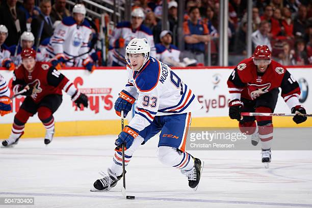 Ryan NugentHopkins of the Edmonton Oilers skates with the puck ahead of Anthony Duclair of the Arizona Coyotes during the NHL game at Gila River...