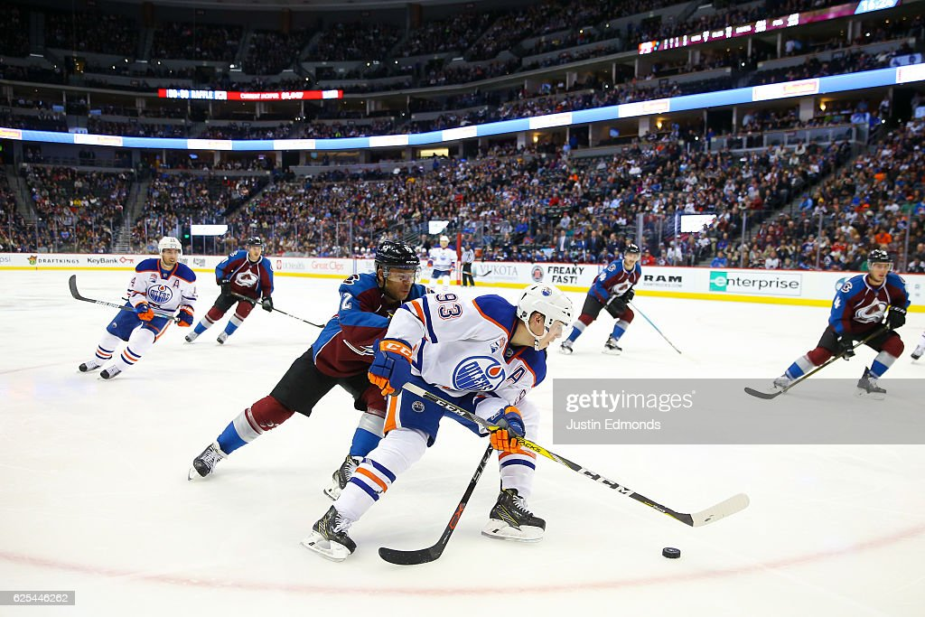 Ryan Nugent-Hopkins #93 of the Edmonton Oilers skates with the puck past Jarome Iginla #12 of the Colorado Avalanche during the third period at Pepsi Center on November 23, 2016 in Denver, Colorado. The Oilers defeated the Avalanche 6-3.