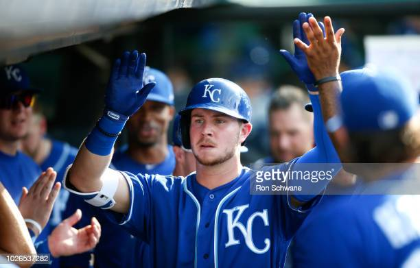 Ryan O'Hearn of the Kansas City Royals gets congratulations in the dugout after hitting a solo home run off starting pitcher Adam Plutko of the...