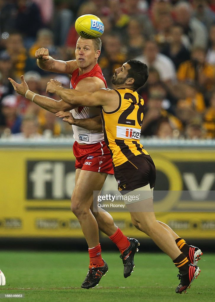 Ryan O'Keefe of the Swans handballs whilst being tackled by Paul Puopolo of the Hawks during the round seven AFL match between the Hawthorn Hawks and the Sydney Swans at Melbourne Cricket Ground on May 11, 2013 in Melbourne, Australia.