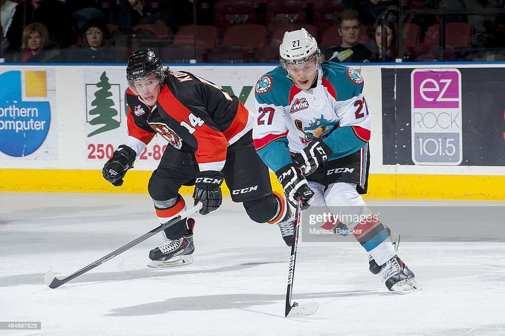 Ryan Olsen #27 of the Kelowna Rockets skates with the puck while back checked by Miles Koules #14 of the Medicine Hat Tigers on January 24, 2014 at Prospera Place in Kelowna, British Columbia, Canada.