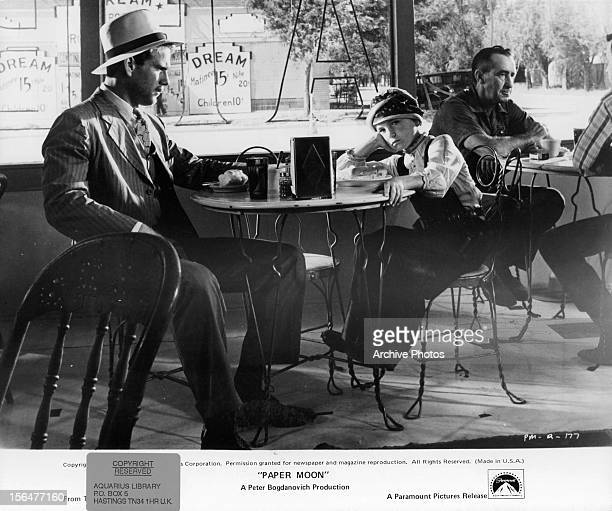 Ryan O'Neal and Tatum O'Neal sitting at a table at a cafe in a scene from the film 'Paper Moon' 1973