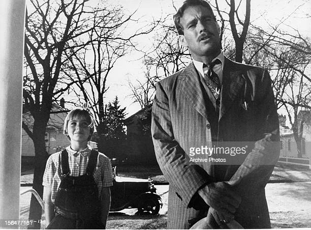 Ryan O'Neal and Tatum O'Neal standing at a door waiting for a response in a scene from the film 'Paper Moon' 1973