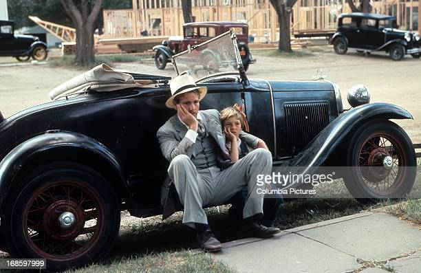 Ryan O'Neal sits with Tatum O'Neal in a scene from the film 'Paper Moon' 1973
