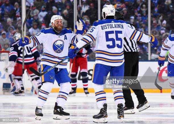 Ryan O'Reilly and Rasmus Ristolainen of the Buffalo Sabres celebrate Ristolainen's third period goal during the 2018 Bridgestone NHL Winter Classic...