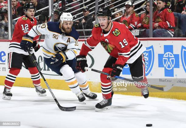 Ryan O'Reilly of the Buffalo Sabres chases the puck against Alex DeBrincat and Jonathan Toews of the Chicago Blackhawks in the first period at the...