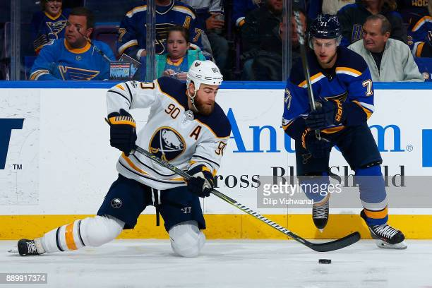 Ryan O'Reilly of the buffalo Sabres clears the puck against Vladimir Sobotka of the St Louis Blues at Scottrade Center on December 10 2017 in St...