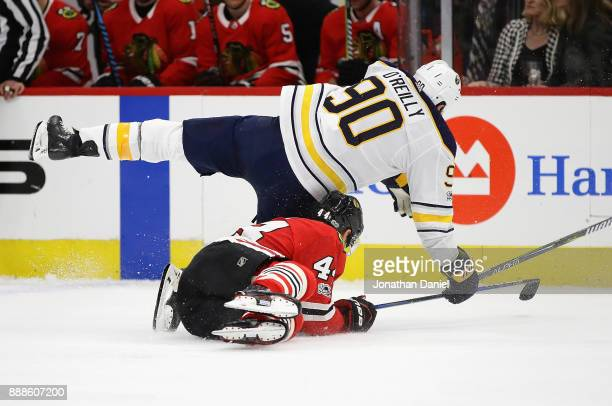 Ryan O'Reilly of the Buffalo Sabres collides with Jan Rutta of the Chicago Blackhawks at the United Center on December 8 2017 in Chicago Illinois