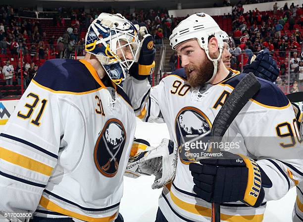 Ryan O'Reilly of the Buffalo Sabres congratulates winning goaltender Chad Johnson following their victory over the Carolina Hurricanes at PNC Arena...