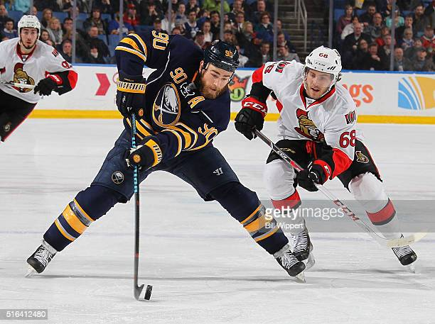 Ryan O'Reilly of the Buffalo Sabres controls the puck while being pursued by Mike Hoffman of the Ottawa Senators during an NHL game on March 18 2016...