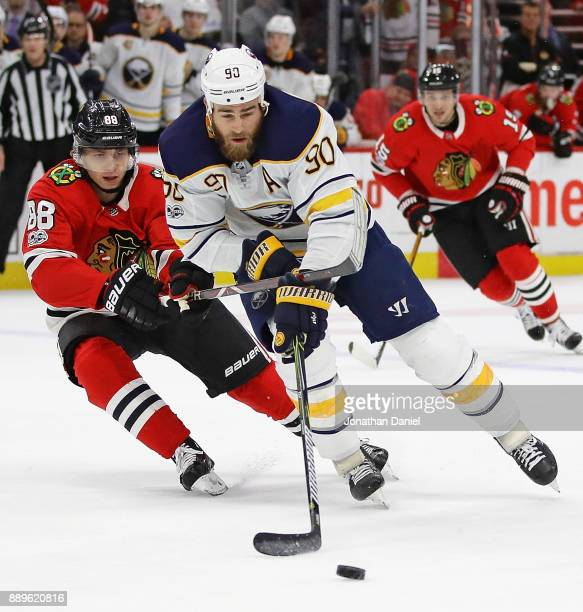 Ryan O'Reilly of the Buffalo Sabres is pressured by Patrick Kane of the Chicago Blackhawks at the United Center on December 8 2017 in Chicago...