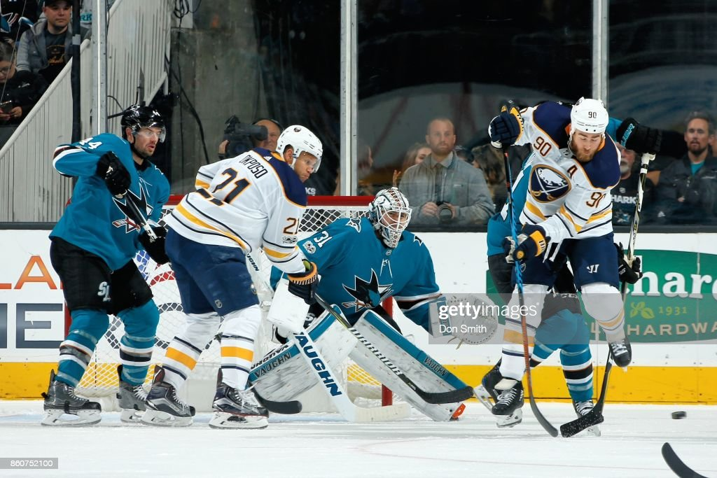 Ryan O'Reilly #90 of the Buffalo Sabres jumps to get out of the way of the puck while teammate Kyle Okposo #21 looks and Marc-Edouard Vlasic #44 and Martin Jones #31 of the San Jose Sharks defend at SAP Center at San Jose on October 12, 2017 in San Jose, California.