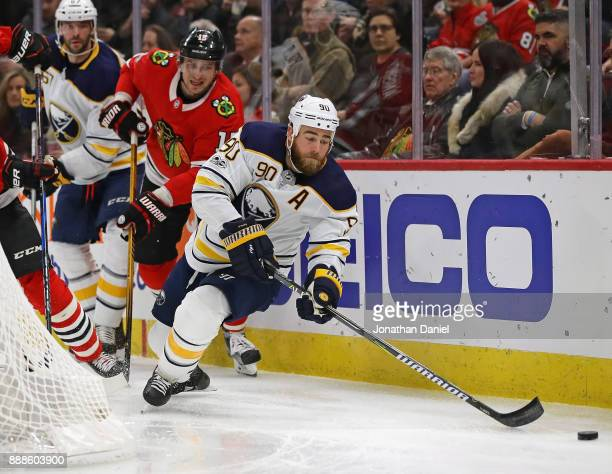 Ryan O'Reilly of the Buffalo Sabres moves to the puck under in front of Artem Anisimov of the Chicago Blackhawks at the United Center on December 8...