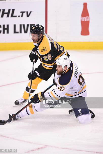 Ryan O'Reilly of the Buffalo Sabres shoots the puck against Dominic Moore of the Boston Bruins at the TD Garden on November 7 2016 in Boston...