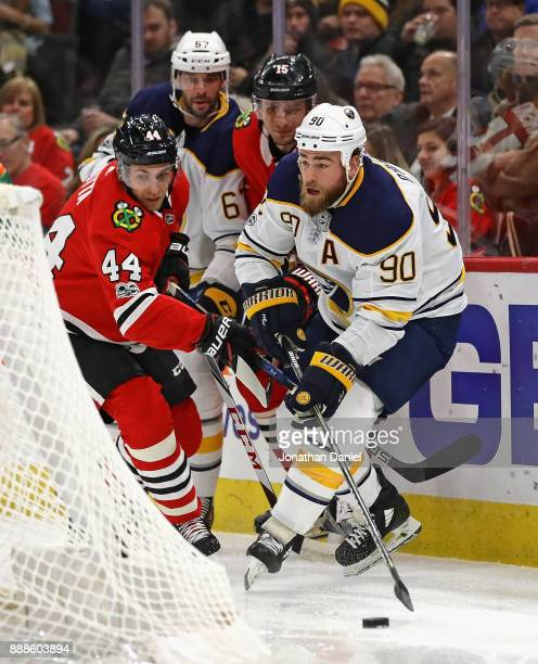 Ryan O'Reilly of the Buffalo Sabres trie to control the puck under pressure from Jan Rutta of the Chicago Blackhawks at the United Center on December...