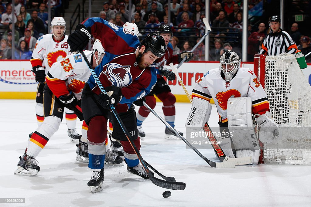 Ryan O'Reilly #90 of the Colorado Avalanche controls the puck as goalie Karri Ramo #31 of the Calgary Flames defends the goal at Pepsi Center on March 14, 2015 in Denver, Colorado.