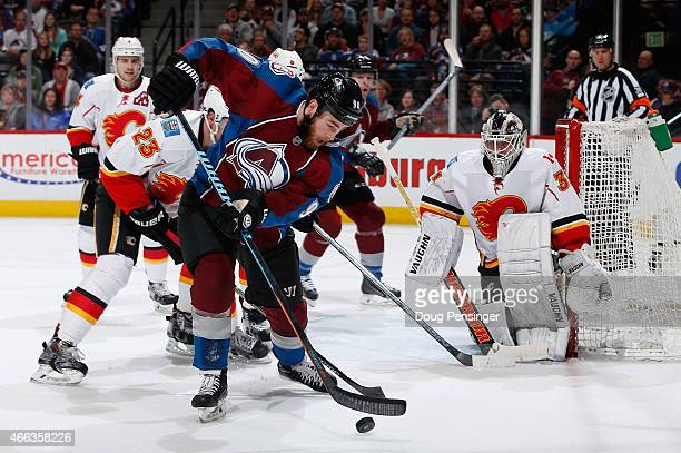 Ryan O'Reilly of the Colorado Avalanche controls the puck as goalie Karri Ramo of the Calgary Flames defends the goal at Pepsi Center on March 14...