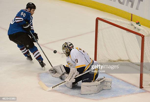 Ryan O'Reilly of the Colorado Avalanche tries to gain control of a loose puck in front of Marek Mazanec of the Nashville Predators in the second...