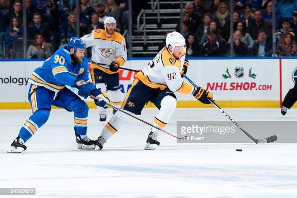 Ryan O'Reilly of the St. Louis Blues battles Ryan Johansen of the Nashville Predators for the puck at Enterprise Center on November 23, 2019 in St....