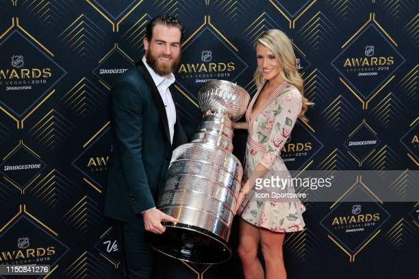 Ryan OReilly of the St Louis Blues poses for photos on the red carpet holding the Stanley Cup trophy with his wife Dayna Douros during the 2019 NHL...