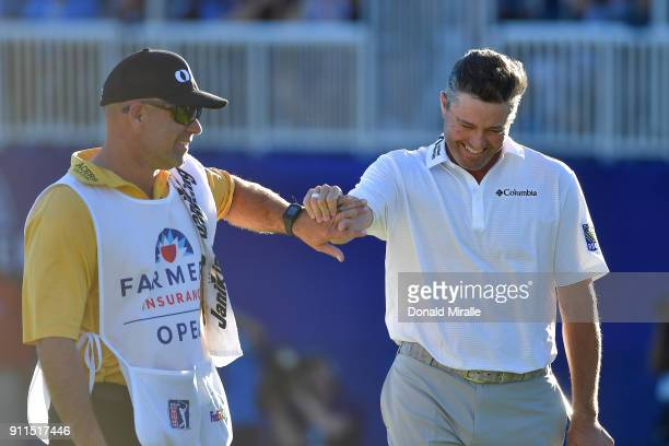 Ryan Palmer laughs with his caddie after making a birdie on the 18th hole during the final round of the Farmers Insurance Open at Torrey Pines South...