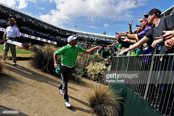 Ryan Palmer throws money to spectators on the 16th hole during the third round of the Waste Management Phoenix Open at TPC Scottsdale on February 1...